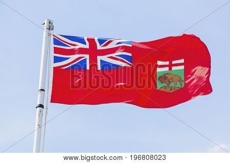 Manitoba flag against blue sky. Winnipeg Manitoba Canada.