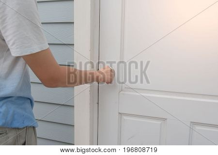 hand open the white door knob or opening the door.