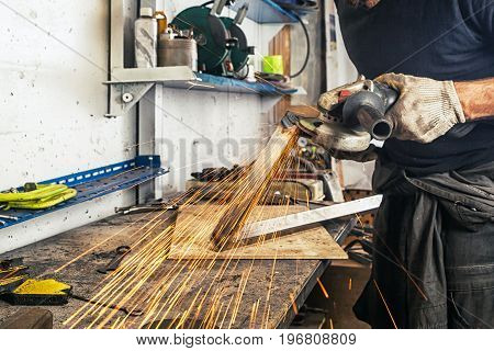 An adult man in work clothes and protective green glasses is engaged in manual labor and grinder metal an angle grinder on a wooden table in the factory yellow sparks fly apart