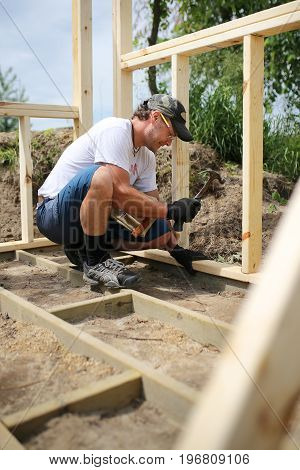 A DIY Carpenter man is hammering nails as he builds the wood frame and sub floor for a backyard garden shed.