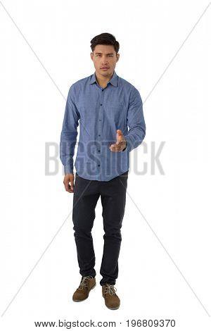 Full length portrait of businessman extending arm for handshake while standing against white background
