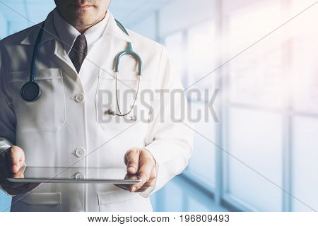 Male Doctor Holding Tablet Computer