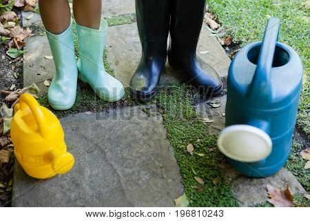 Low section of senior woman and granddaughter standing by watering cans on walkway at backyard