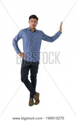 Portrait of young businessman standing with hand on hip against white background