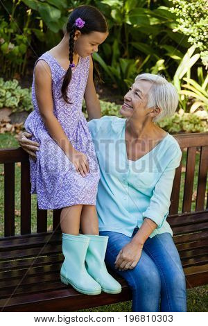 Grandmother and granddaughter sitting on wooden bench at backyard