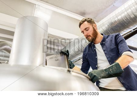 manufacture, business and people concept - man working at craft brewery or beer plant