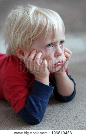A bored and grumpy toddler child is laying on the carpet at home pulling on his cheeks and making a pouting face.