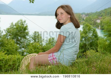 a pretty pre teen girl sitting in grass