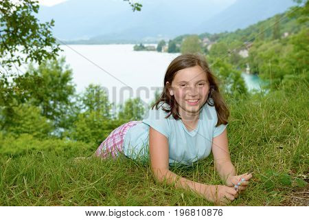 pretty smiling pre teen girl lying in grass