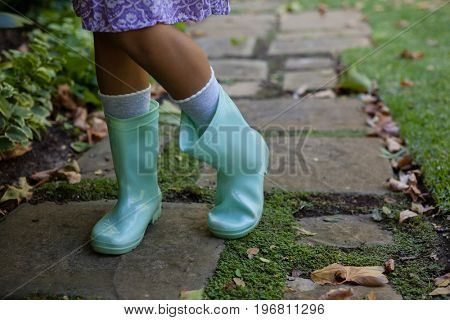 Low section of girl wearing green rubber boots standing on walkway at backyard