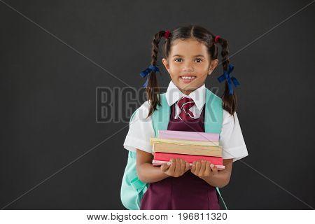 Portrait of schoolgirl in school uniform holding books against blackboard in classroom