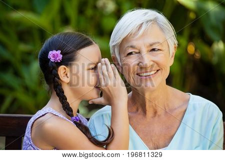 Granddaughter whispering in ears of smiling grandmother at backyard