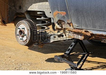 A rusty old car is raised up on a jack for a tire change after getting a flat tire.