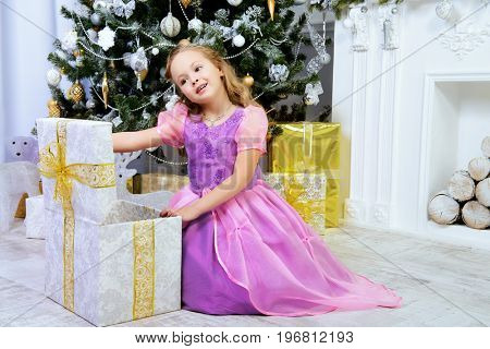 Happy little girl in a beautiful dress near the Christmas tree opening her gift box. Christmas miracles. Luxurious Christmas decoration.