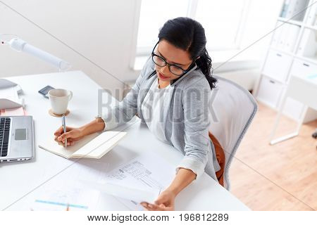 business, technology, communication and people concept - businesswoman or secretary calling on smartphone and writing to notebook at office