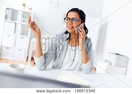 business, communication and people concept - happy businesswoman or secretary calling on smartphone at office