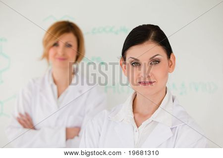 Two Cute Women In Front Of A White Board