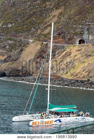 PORTO MONIZ MADEIRA PORTUGAL - SEPTEMBER 5 2016: Catamaran while sailing with tourists docked in Porto Moniz. Madeira Porttugal