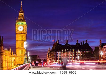 London Big Ben and westminster street crowd and traffic night life. Long exposure of speed motion people walking and cars driving on bridge. Europe travel destination.