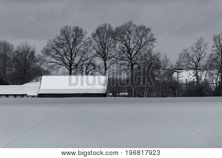 Old Black And White Photo Of Dutch Farmland With Farm Covered In Snow.