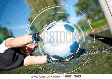 sport and technology - soccer player or goalkeeper lying with ball at football goal on field