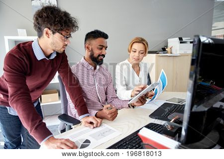 business, technology and people concept - international creative team with papers and tablet pc computer and papers in office