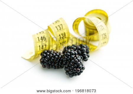 Tasty ripe blackberries and measuring tape isolated on white background.