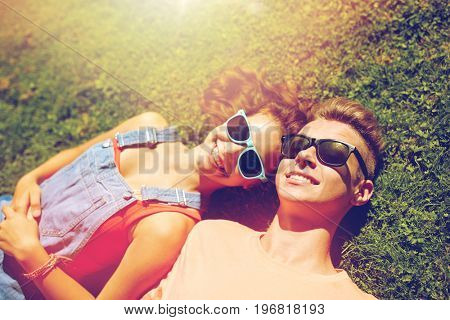 love and people concept - happy teenage couple in sunglasses lying on grass at summer