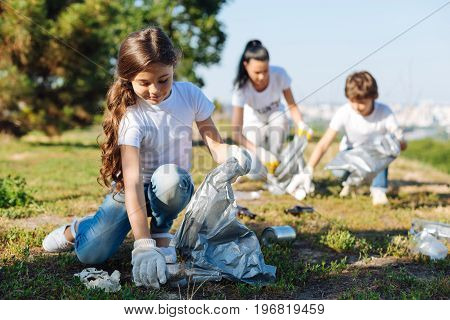 Clean our planet. Longhaired brunette keeping smile on her face and bowing head while gathering rubbish into plastic bag
