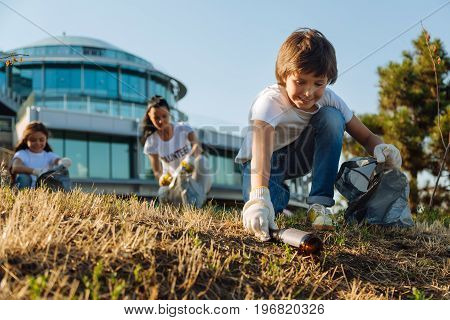 Sort all rubbish. Pleased kids taking glass bottle, helping his friends in participating in earth cleaning