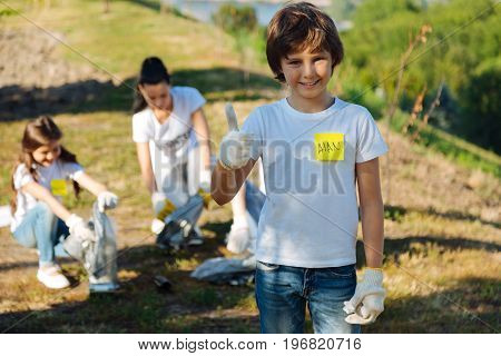 Be like us. Handsome kid keeping smile on his face and showing his thumb while his friends gathering rubbish into plastic bag