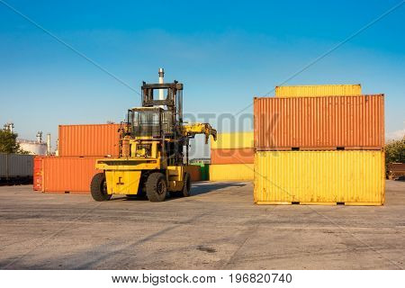 Handling container stack in shipping yard and forklift operating.