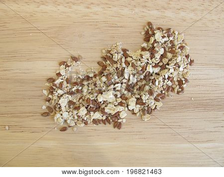 Seed mixture with rolled oats, flaxseeds, and sesame on wooden board
