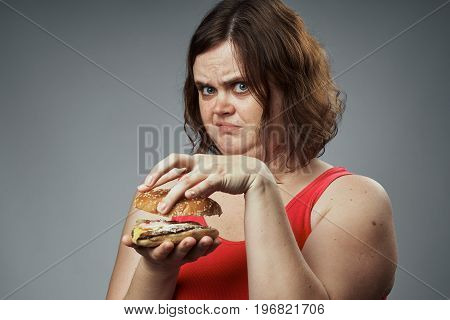 Fat woman on a gray background holds a hamburger, fast food.
