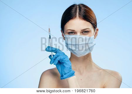 Beautiful young woman on a blue background holds a syringe, plastic surgery, medicine.