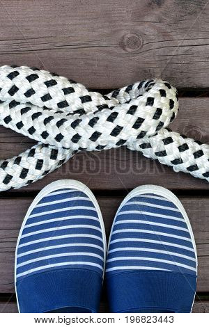 Blue and white striped sailor style shoes and rope with a knot on a brown wooden dock. Vertical image.