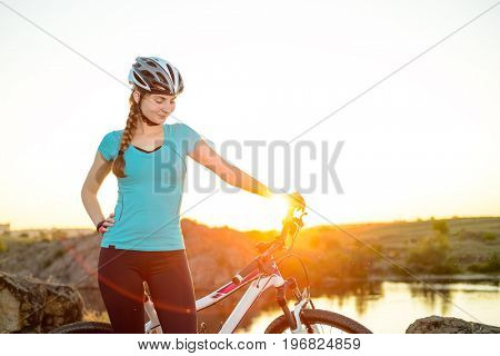 Young Woman with Mountain Bike on the Summer Rocky Trail at Beautiful Sunset. Travel, Sports and Adventure Concept.