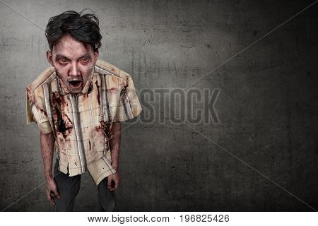 Scary and bloody asian zombie man against dark wall background