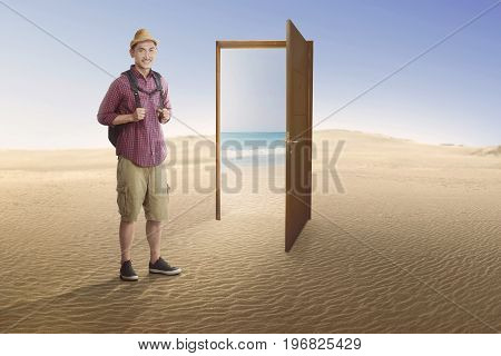 Traveler asian man going to beach on the open door at desert