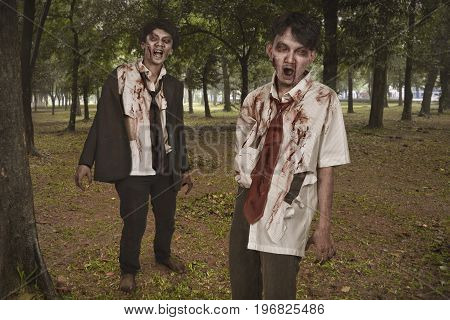 Two creepy and bloody asian zombies in clothes on the woods