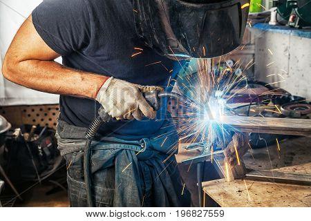 Man Welds With A Welding Machine Metal