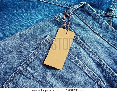 Blank label price tag on blue jeans from recycled paper. Mockup for price or brand presentation.