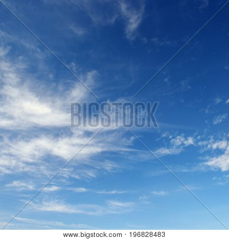 White cirrus clouds against  dark blue sky. background.