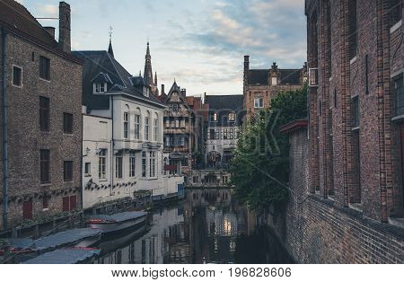 Evening view of typical canal of medieval city of Brugge with traditional houses