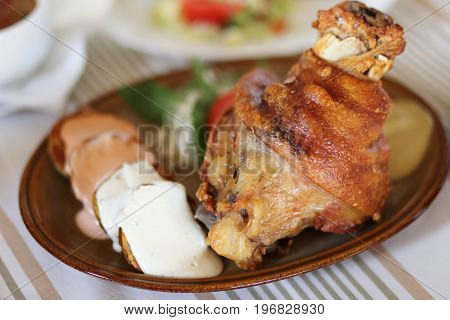 Baked Pork Knee - traditional Slovakian dish served with backed potato sause and cabbage salad