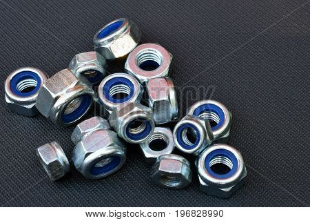 Nylon locking nuts on dark surface with room for text.