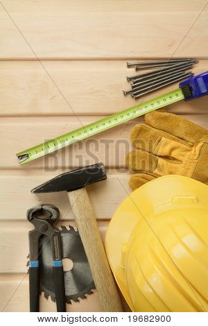 Working tools on a wooden boards background. Including saw, ruler, helmet, nails, pliers,hammer.