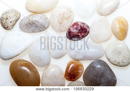 Quartz beach pebbles in close up. Natural world backdrop image. Small beach stones with various textures and patterns against whit background.