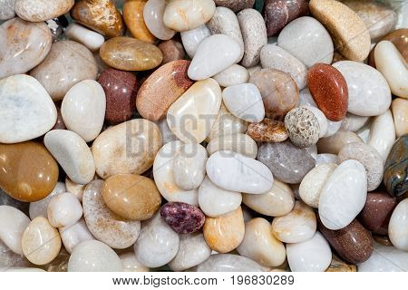 Selection of polished beach pebbles. Decorative garden aggregate used for ornamental ground cover. High quality rounded stones. Background natural world pattern image.
