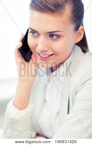 picture of smiling businesswoman with smartphone in office